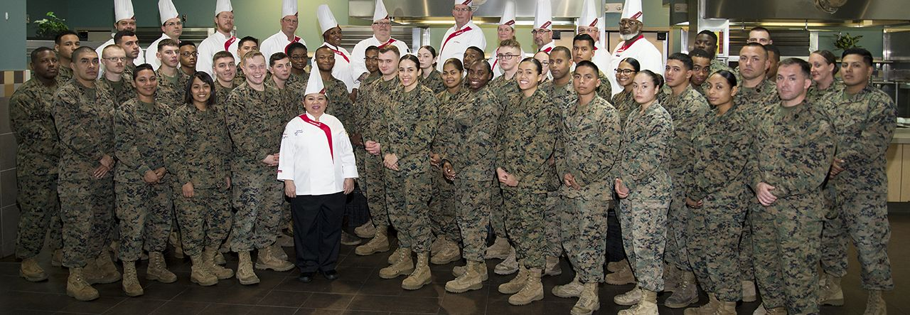 Group of male and female soldiers and military chefs posing together for a group photo