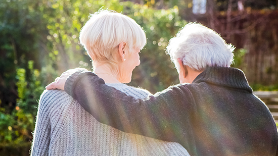 A male and female elderly person hugging each other, view from behind